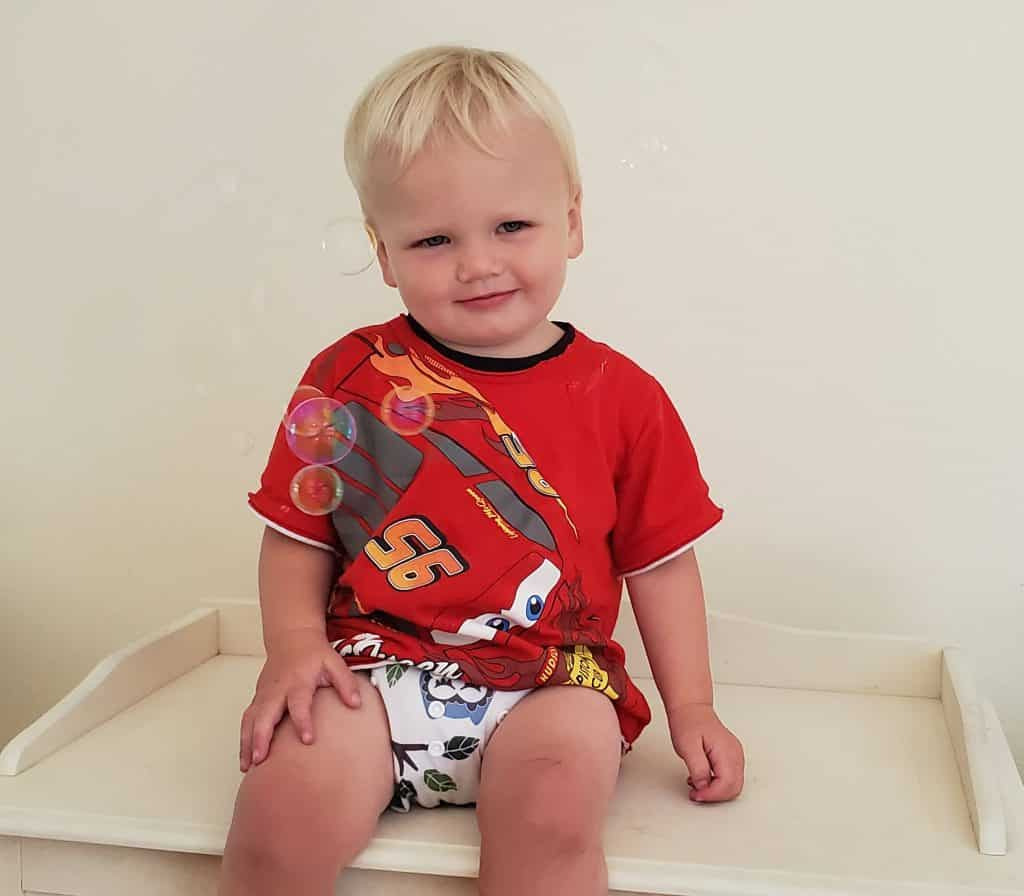kid sitting with a cloth diaper