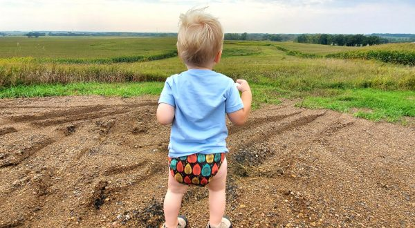 child in a field with a diaper