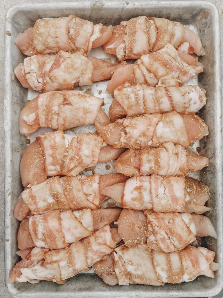 raw bacon wrapped chicken ready for oven